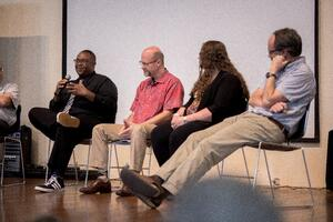 Faculty sit on stage for a panel discussion